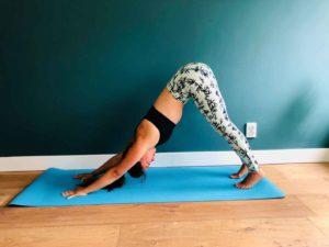 Downward facing dog yoga oefening dame op mat doet oefening